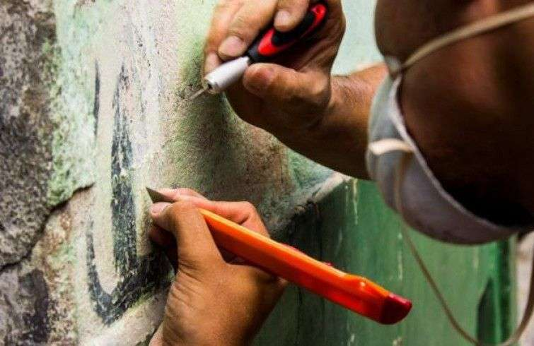 Restorers used a method known as stacco to detach the graffiti from the wall.