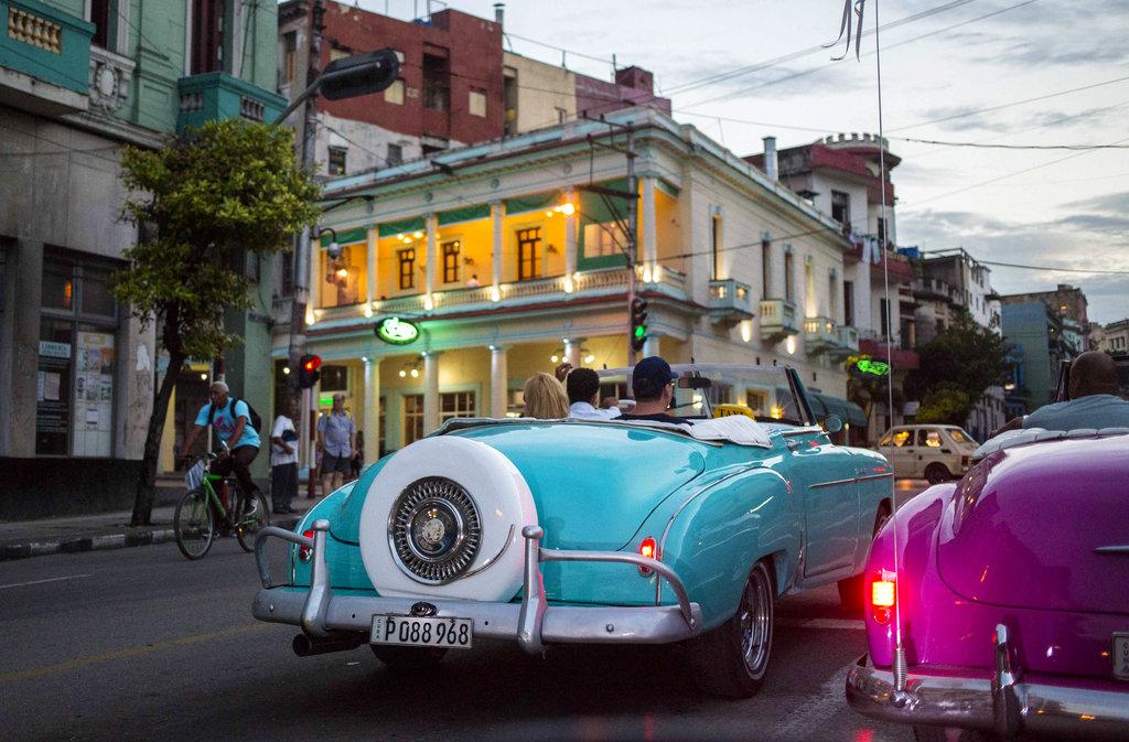 Tourists in vintage American convertibles in Havana. Photo: Desmond Boylan / AP.