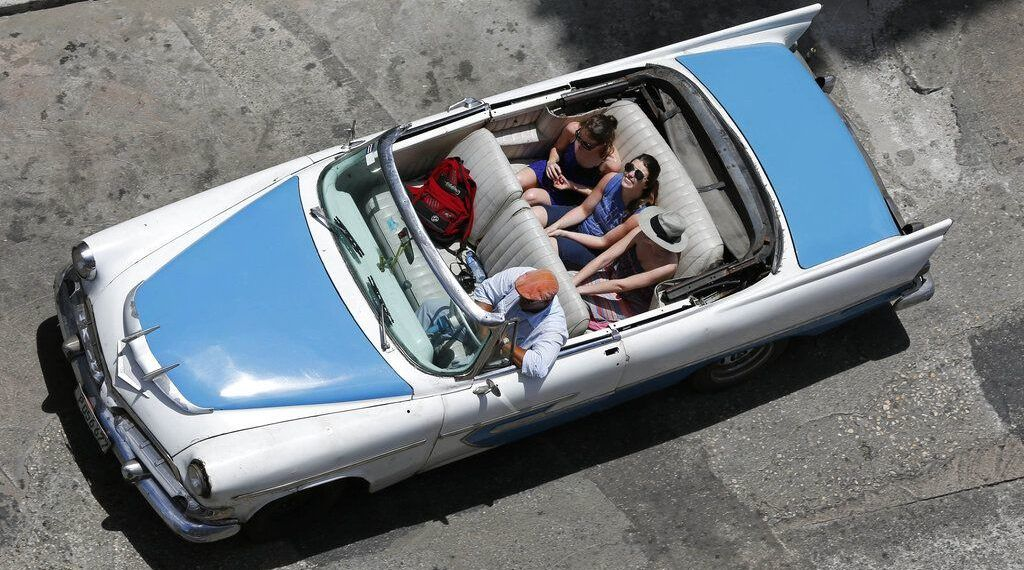 In this picture taken on May 13, 2015, tourists stroll in a classic convertible in Havana. Photo: Desmond Boylan / AP.