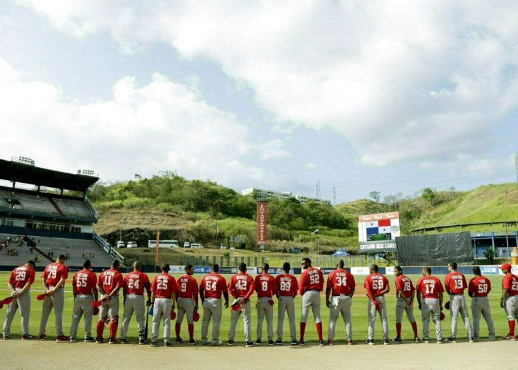Players of the Cuban Las Tunas Leñeros team listening to their national anthem before facing Panama's Los Toros de Herrera in the finals of the Caribbean Series at the Rod Carew Stadium in Panama City, on February 10, 2019. Photo: Arnulfo Franco/AP.