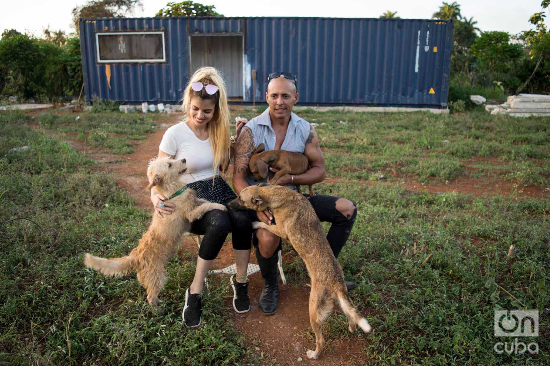 Venus and Ernesto with several of the dogs from their shelter. Behind, the container that will adapt as a house while they build their new home. Photo: Otmaro Rodríguez.