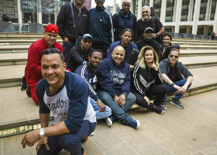 Members of Los Van Van band, with the leader of the group Samuel Formell, at the front, pose at the Lincoln Center in New York on Tuesday, June 25, 2019. Photo: Bebeto Matthews / AP.