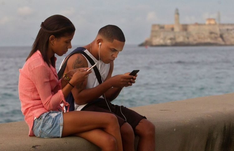 A young couple connects to the internet from the Malecón seawall, on December 27, 2018, in Havana. Photo: Yander Zamora / EFE.