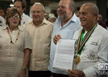 Chef Eddy Fernández (r), president of the Culinary Federation of Cuba, shows the document that accredits Cuban cuisine as national Cultural Heritage. Next to him, Cuban Minister of Tourism Manuel Marrero (second to the right) and Gladys Collazo, president of the National Cultural Heritage Council (l), among other personalities. Photo: Otmaro Rodríguez.
