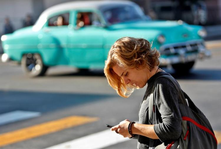 A woman uses her cell phone this Friday, December 6, 2019, in Havana, one year since the activation of mobile internet in Cuba. Photo: EFE / Yander Zamora.