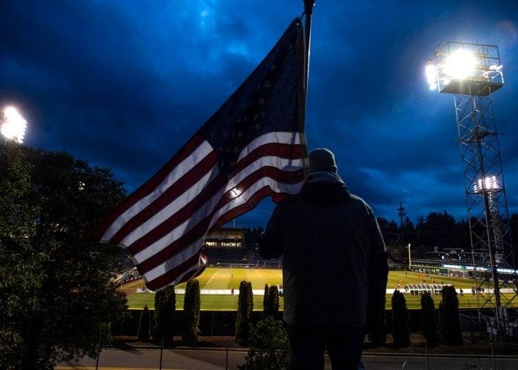 A man holds the United States flag while following a United States Football League game in Tacoma, Washington. Photo: Joshua Bessex/The News Tribune via AP.