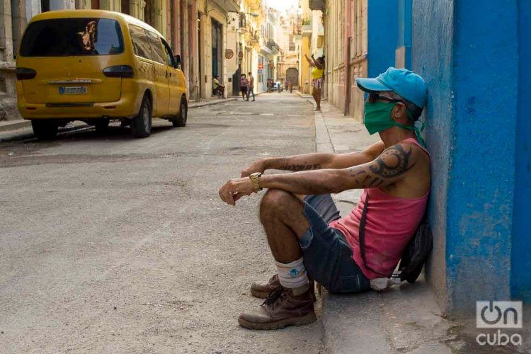 A man sitting on a sidewalk in Havana, with a facemask as a measure of protection against the coronavirus pandemic. Photo: Otmaro Rodríguez.