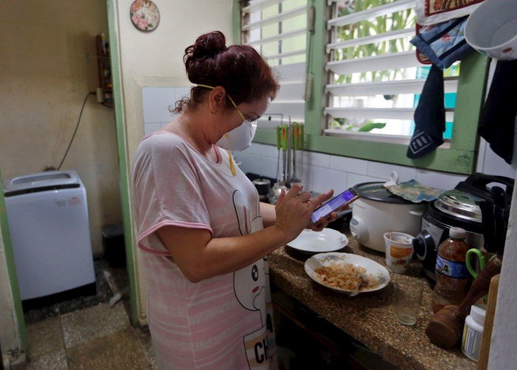 A woman checks her phone in the kitchen of her home on April 6, 2020 in Havana. Photo: EFE/Ernesto Mastrascusa