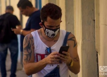 A Cuban checks his cell phone in Havana wearing a facemask as a protection measure against the COVID-19 pandemic. Photo: Otmaro Rodríguez.