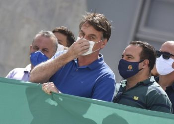 President Jair Bolsonaro touching his facemask during a protest against the Federal Supreme Court and the National Congress in Brasilia. Photo: André Borges/AP.