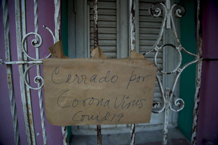 "A sign saying ""Closed for coronavirus COVID-19"" hangs on the window of a business in Havana, Cuba, on Friday, April 24, 2020. (AP Photo/Ismael Francisco)"