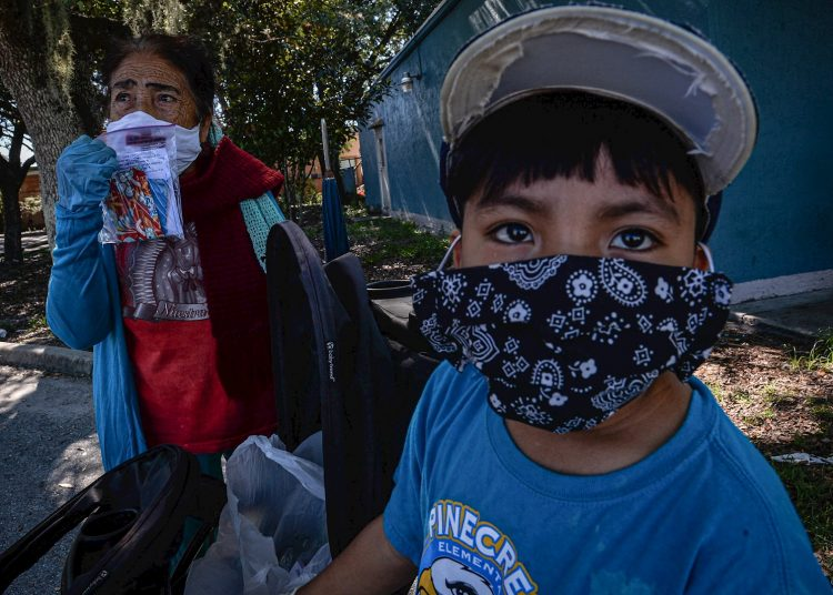 """Esperanza Miranda and her grandson wear facemasks to protect themselves from contagion on June 17, 2020 in Immokalee, in South Florida. At the cost of their health, thousands of Mexican and Central American immigrants who are declared """"essential"""" managed to collect this year's harvest in Immokalee, the tomato capital of the United States and now also one of the hottest spots for the COVID-19 in Florida. Photo: Giorgio Viera/EFE."""