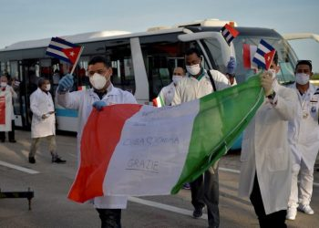 Cuban doctors wave Cuban and Italian flags after their arrival in Havana from Europe this Monday. Photo: Yamil Lage/EFE