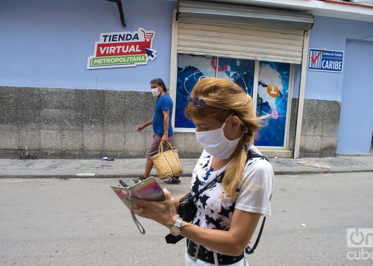 Two people walk wearing facemasks in Havana, as protection against the coronavirus pandemic. Photo: Otmaro Rodríguez.