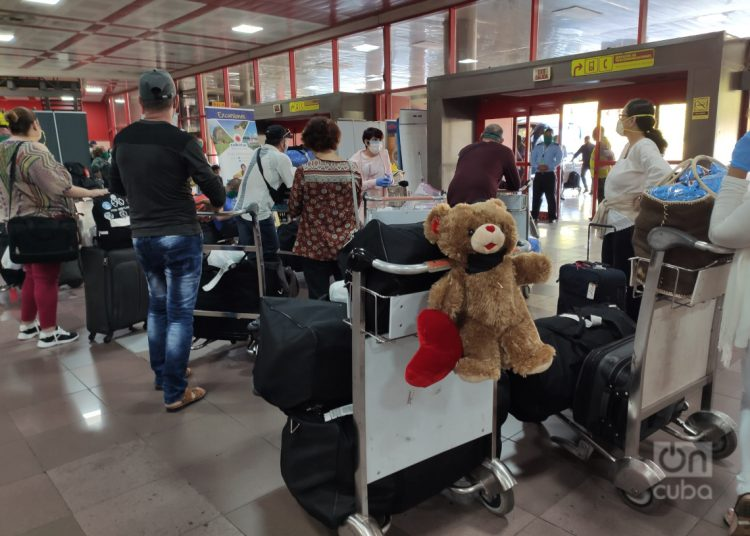 Cubans who arrived on the island, with a single suitcase weighing 23 kilograms each, waiting at Havana's José Martí airport for their transfer to an isolation center for the quarantine because of COVID-19 before going home. Photo: Mónica Rivero.