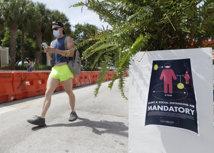 A person wearing a mask walks along Miami Beach, Florida, on Saturday, July 4, 2020. (AP Photo/Wilfredo Lee)
