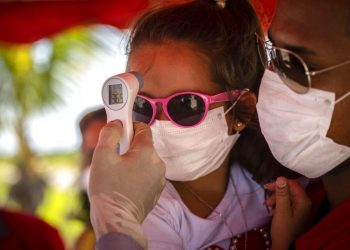 A girl wearing a mask to protect her from the new coronavirus has her temperature taken at a police checkpoint. This was at the entrance to the province of Havana, Cuba, on Monday, August 10, 2020.