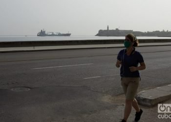 A woman jogs in Havana, wearing a mask as a protection measure against the coronavirus pandemic. Photo: Otmaro Rodríguez