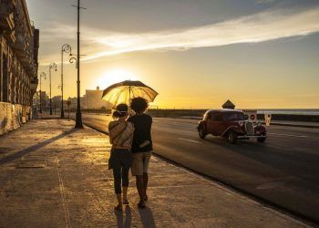 A couple wearing masks hold an umbrella as they walk along the boardwalk at sunset in Havana, Cuba, Monday, Aug. 31, 2020. Photo: Ramón Espinosa/AP