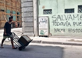 A young man wearing a face mask carries a television on a wheelbarrow in Havana. Photo: Ernesto Mastrascusa/EFE.
