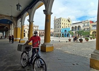 A man with a mask walks his bicycle through a square in Old Havana. Photo: Ernesto Mastrascusa/EFE.