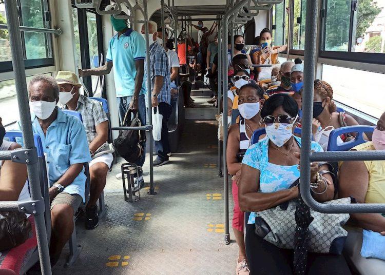 Dozens of people wear face masks on Monday while riding an urban transportation bus in Havana. Photo: Ernesto Mastrascusa/EFE.