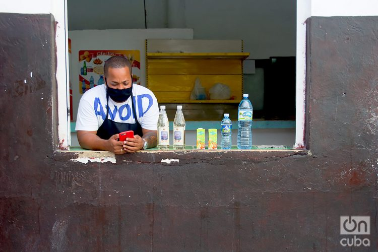 A clerk wearing a mask checks his mobile phone, after the relaxation of restrictions due to COVID-19 in Havana. Photo: Otmaro Rodríguez.