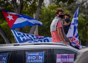 """Some young people listen to the speech of former United States President Barack Obama, sitting on the roof of a car decorated with posters that say """"Cubans for Biden Harris,"""" during a rally in support of Democratic presidential candidate Joe Biden, in the Biscayne Campus of Florida International University (FIU) in Miami, Florida. Photo: Giorgio Viera/EFE."""