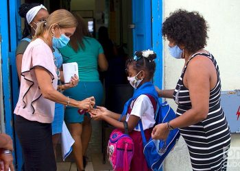 An educator applies a disinfectant to a girl's hands at the entrance to her school in Havana. Photo: Otmaro Rodríguez.