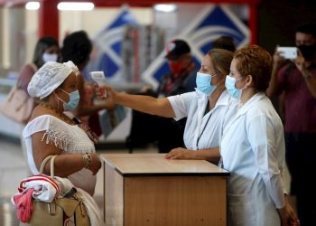 Workers at the Havana airport take the temperature of a female traveler after the restart of regular operations, suspended for months due to the pandemic. Photo: EFE/Yander Zamora/Archive.