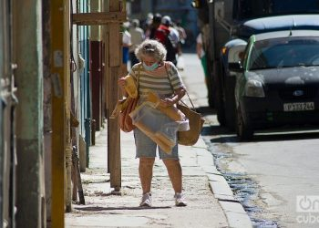 An elderly woman with bread and other purchases walks down a street in Havana during the outbreak of COVID-19 in January 2021. Photo: Otmaro Rodriguez.