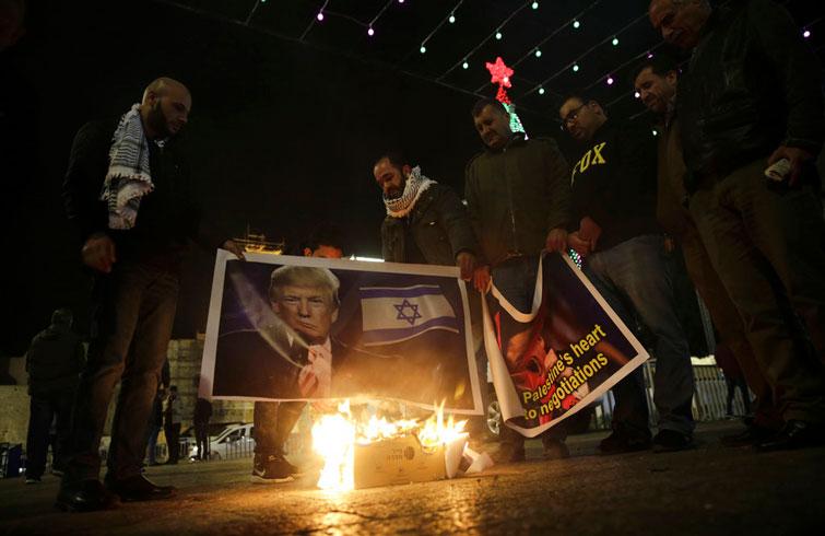 Varios palestinos queman un afiche con la imagen del presidente estadounidense Donald Trump y la bandera israelí durante una protesta en Belén, Cisjordania, contra el anuncio de que Estados Unidos reconocerá a Jerusalén como la capital israelí. Foto: Mahmoud Illean / AP.