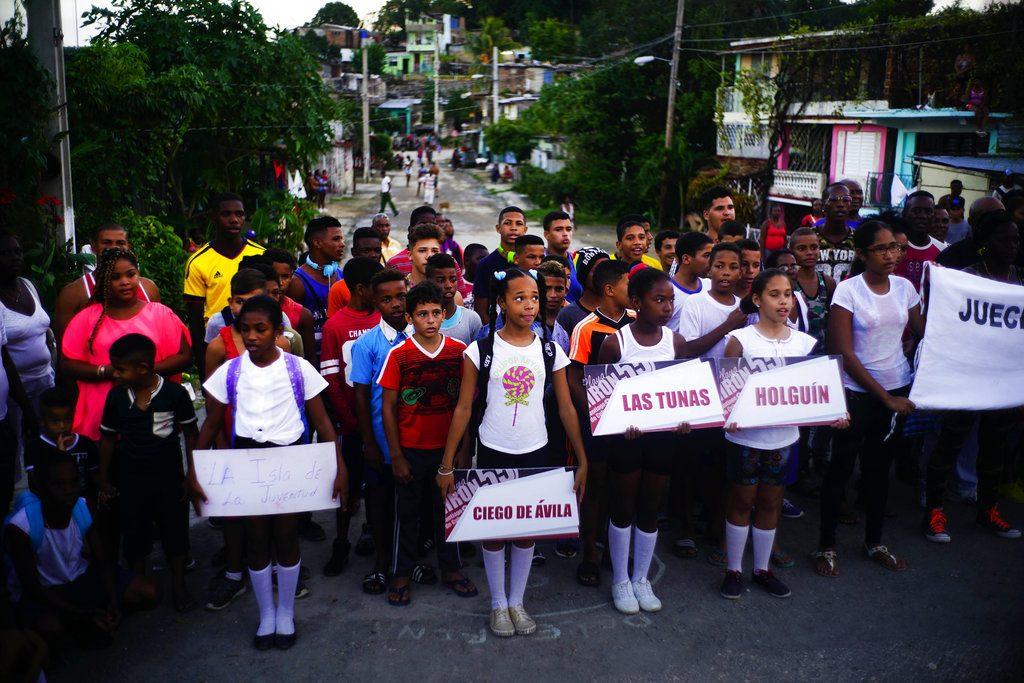 Niños locales sostienen carteles con los nombres de las provincias de las que proceden los jóvenes luchadores (detrás de ellos) que participan en el torneo de lucha. Foto: Ramón Espinosa / AP.