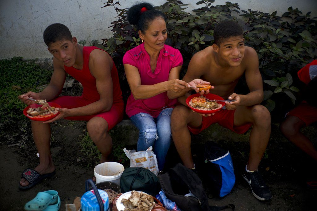 Nalis Mendoza corta un tomate mientras da de comer a sus hijos, que participan en el torneo amateur de lucha de Chicharrones, Santiago de Cuba. Foto: Ramón Espinosa / AP.