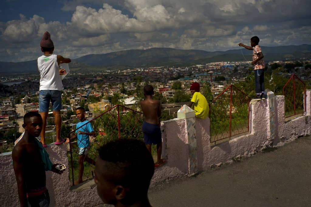 Luchadores de provincias del este y el centro de Cuba descansan junto a niños locales que juegan con papalotes. Foto: Ramón Espinosa / AP.