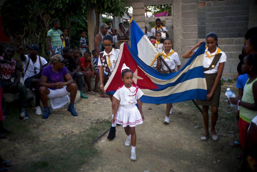 Niñas desfilan con una bandera de Cuba durante la ceremonia de apertura de una competición de lucha de nivel aficionado de una semana de duración organizada en enero por vecinos de Chicharrones, en Santiago de Cuba. Foto: Ramón Espinosa / AP.