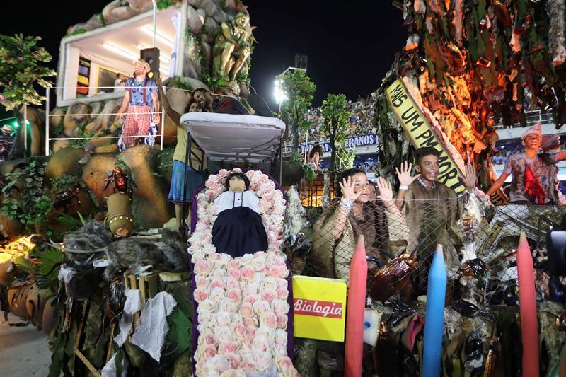 Integrantes de la escuela de samba del Grupo Especial Beija Flor, hace una representación de la violencia en Rio de Janeiro en Rio de Janeiro con ataúd con estudiante muerto y un policia arriba tiroteado hoy, domingo 12 de febrero de 2018, en la celebración del carnaval en el sambódromo de Marques de Sapucaí en Río de Janeiro (Brasil). EFE/ Marcelo Sayão