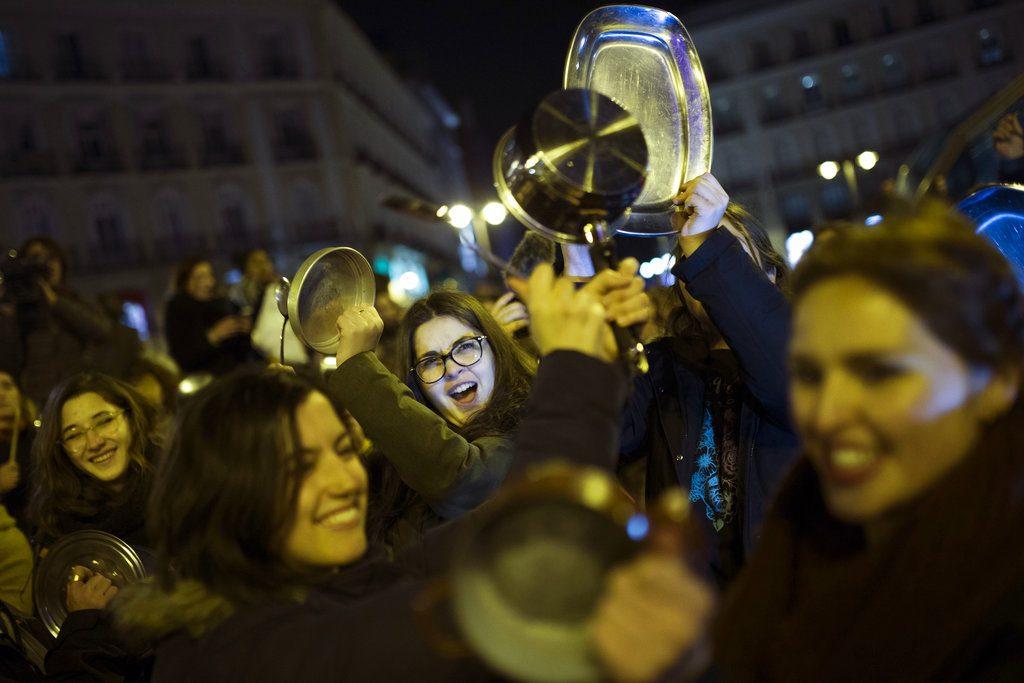Mujeres golpeando cacerolas y sartenes mientras corean lemas durante una protesta marcando el inicio de una huelga de mujeres de 24 horas en la Puerta del Sol de Madrid, en la madrugada del jueves 8 de marzo de 2018. (AP Foto/Francisco Seco)