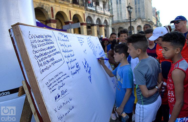 Niños firman mural en recordación a todos los fallecidos de cáncer durante la carrera Terry Fox en La Habana. Foto: Otmaro Rodríguez.