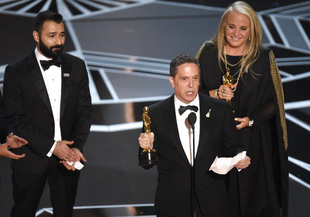 """Adrian Molina, de izquierda a derecha, Lee Unkrich, y Darla K. Anderson reciben el preimio a la mejor película animada por """"Coco"""" en los Oscar. Foto: Chris Pizzello/Invision/AP."""