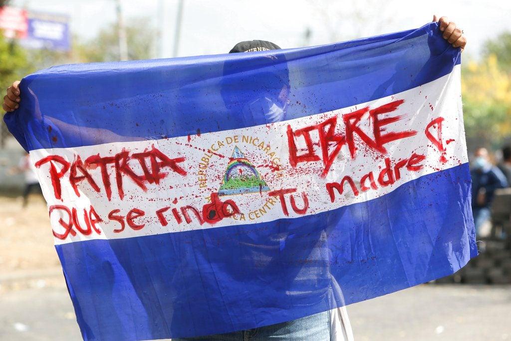 """Un manifestante sostiene una bandera de Nicaragua con la leyenda """"Patria Libre. Que se rinda tu madre!"""" durante choques con las fuerzas de seguridad cerca de la Universidad Politécnica de Nicaragua en la capital Managua, el sábado 21 de abril de 2018. (AP Foto/Alfredo Zúñiga)"""