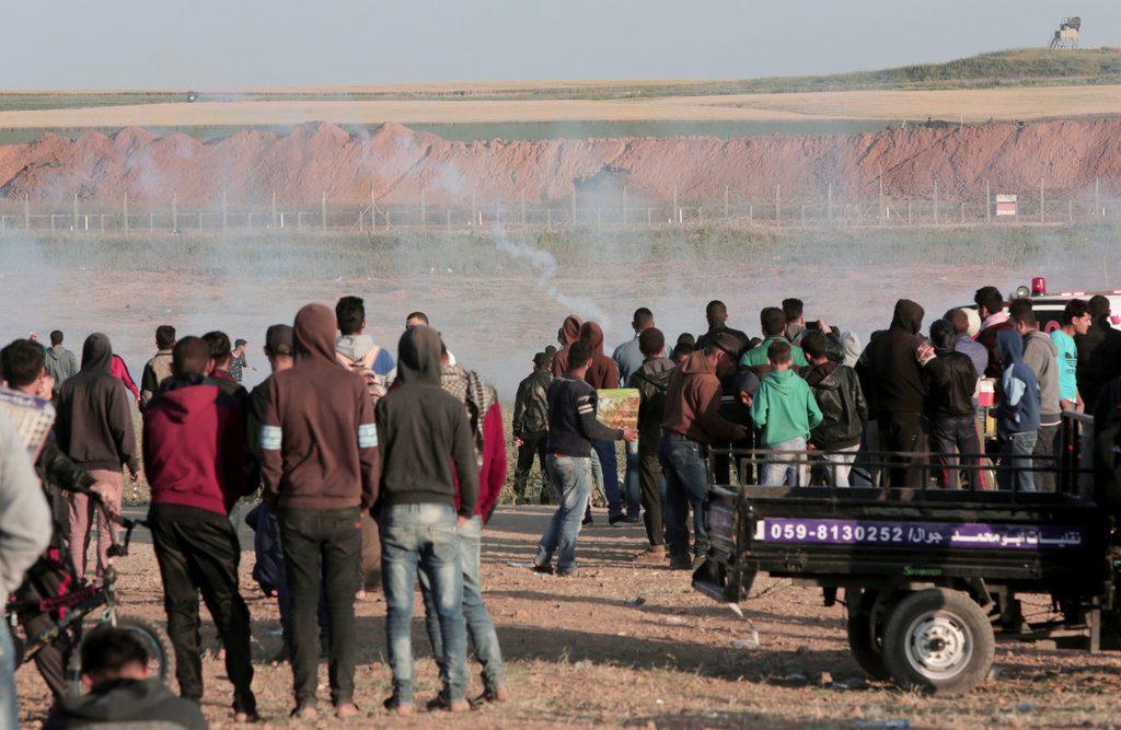 Manifestantes palestinos observan la caída de cargas de gas lacrimógeno disparadas por soldados israelíes durante enfrentamientos en la zona fronteriza de la Franja de Gaza e Israel al este de Beit Lahiya, Gaza, el sábado 31 de marzo de 2018. Foto: Adel Hana / AP.