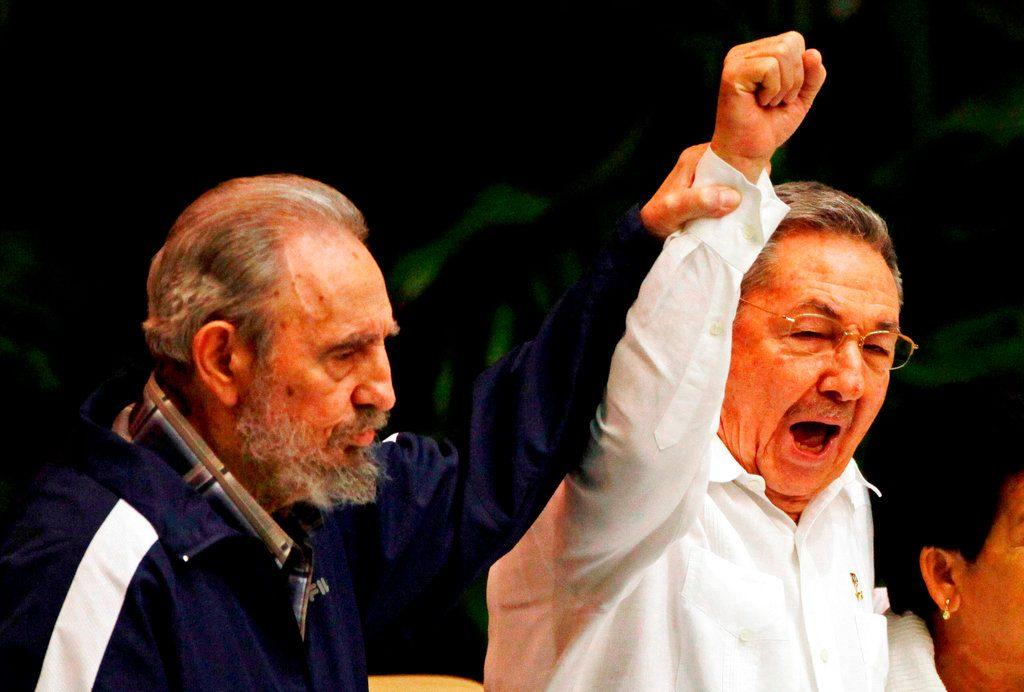 Fidel Castro levanta la mano de su hermano, el presidente de Cuba Raúl Castro, mientras cantan el himno de la internacional socialista durante el VI Congreso del Partido Comunista en La Habana, el 19 de abril de 2011. Foto: Javier Galeano / AP.