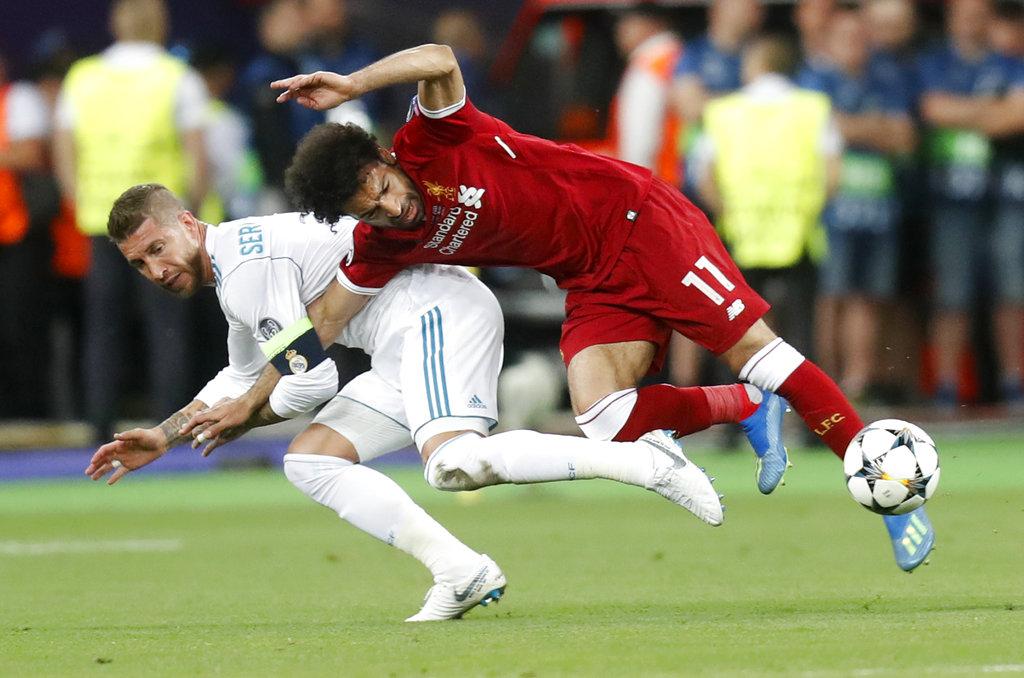Sergio Ramos (izquierda) del Real Madrid comete una falta a Mohamed Salah del Liverpool en la final de la Liga de Campeones, en Kiev, Ucrania, el sábado 26 de mayo de 2018. (AP Foto/Efrem Lukatsky)