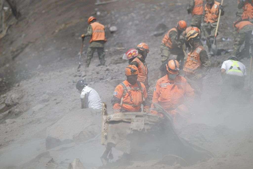 Los bomberos examinan la estabilidad de un área donde antes se encontraba el puente Las Lajas en El Rodeo, Guatemala. Foto: Luis Soto / AP.