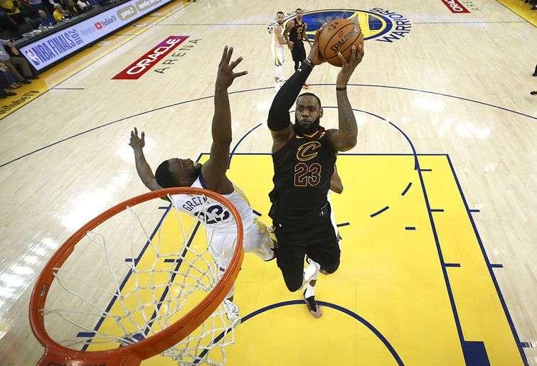 LeBron se eleva para encestar una canasta ante Draymond Green, de los Warriors de Golden State, en el primer partido de la final de la NBA en Oakland, California, el 31 de mayo de 2018. Foto: Ezra Shaw / Pool vía AP.