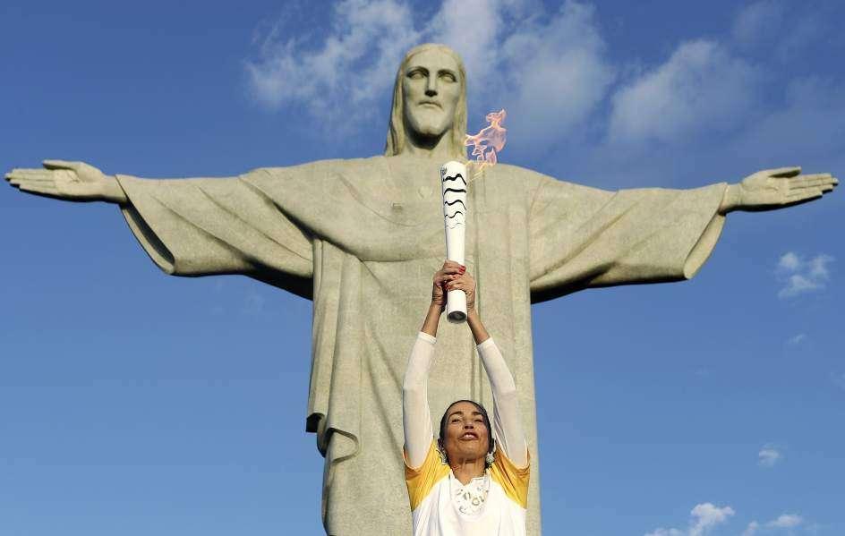 La exjugadora de voleibol brasileña Isabel Barroso Salgado lleva la antorcha olímpica hoy, viernes 05 de agosto de 2016, en el Cristo Redentor, en Río de Janeiro. Foto: EFE.