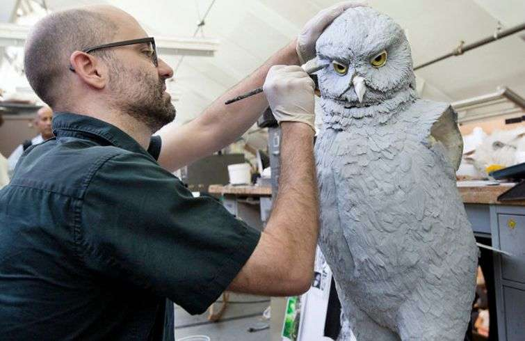 Artist Jason E. Brougham paints a model of a giant owl for the exhibition. Photo: Sara Krulwich / The New York Times.