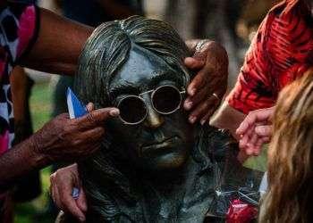 Una mujer sostiene los espejuelos de John Lennon durante el concierto homenaje a los 50 años del disco Sgt. Peppers Lonely Hearts Club Band en La Habana, Cuba. Foto: Fernando Medina / Cubahora.