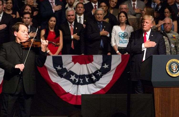 El violinista cubano Luis Haza toca el himno nacional de EE.UU. durante discurso de Donald Trump en el teatro Manuel Artime, el viernes 16 de junio. Foto: Cristobal Herrera / EFE.